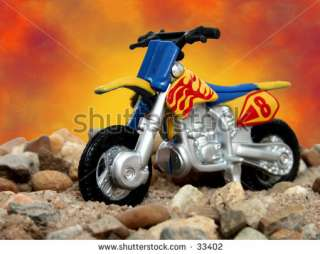 Toy Dirt Bike In Sand And Rock On A Studio Background. Stock Photo